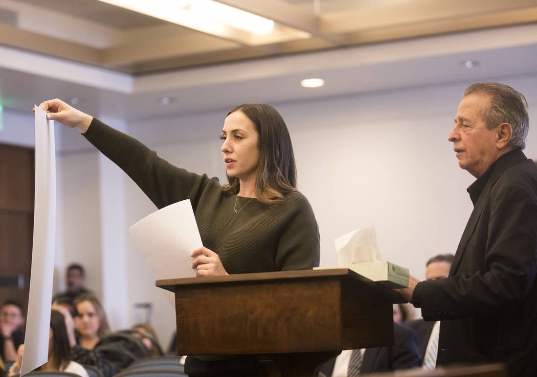 Allie Rossie, sister of A.J. Rossi, holds up a giant photo of A.J. while asking the suspect to ...