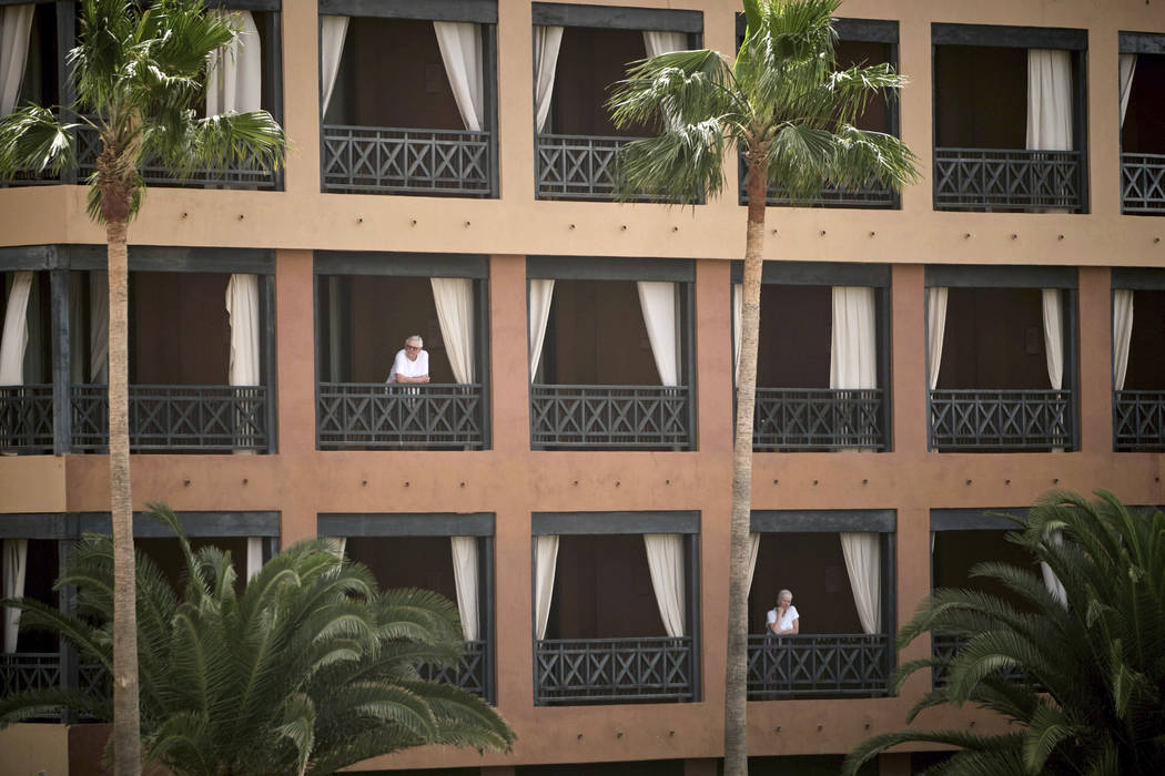 People stand at their balconies at the H10 Costa Adeje Palace hotel in Tenerife, Canary Island, ...