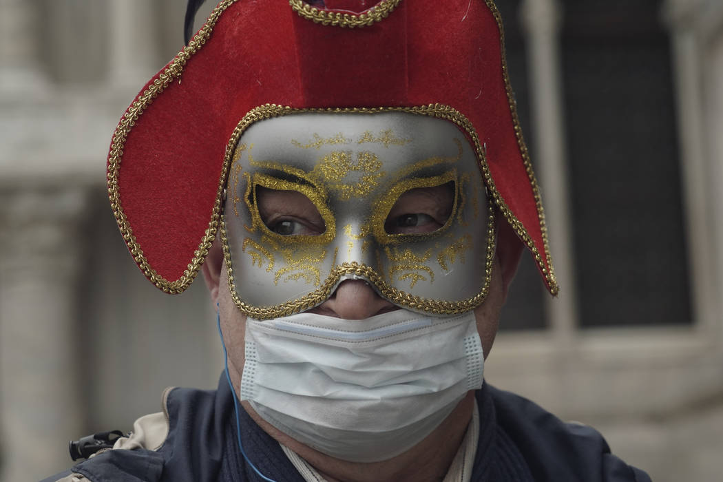A Russian tourist dons both a carnival mask and a protective face mask as he visits St. Mark's ...