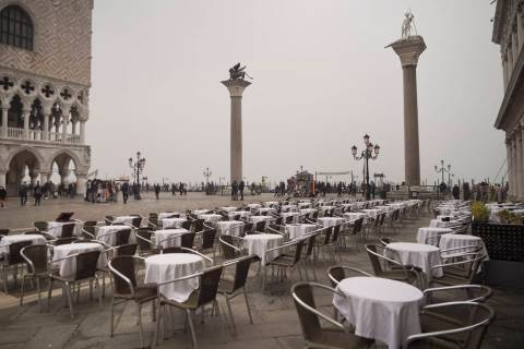 Empty tables sit in St. Mark's square in Venice, Italy, Tuesday, Feb. 25, 2020. Italy has been ...