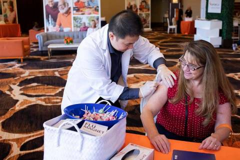 Vons Pharmacy intern Kevin Chang cleans Brenda Julian's upper arm in preparation for a flu shot ...
