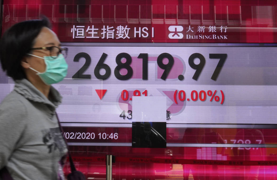 A woman walks past a bank electronic board showing the Hong Kong share index at Hong Kong Stock ...