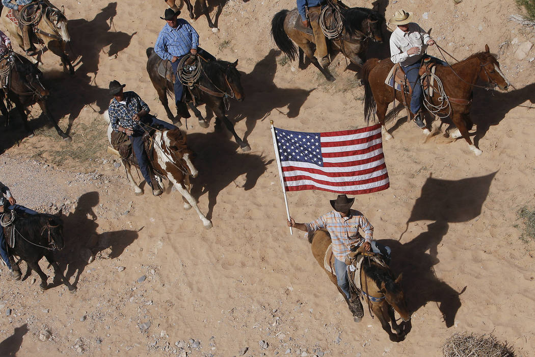 In this April 12, 2014, file photo, the Bundy family and their supporters fly the American flag ...