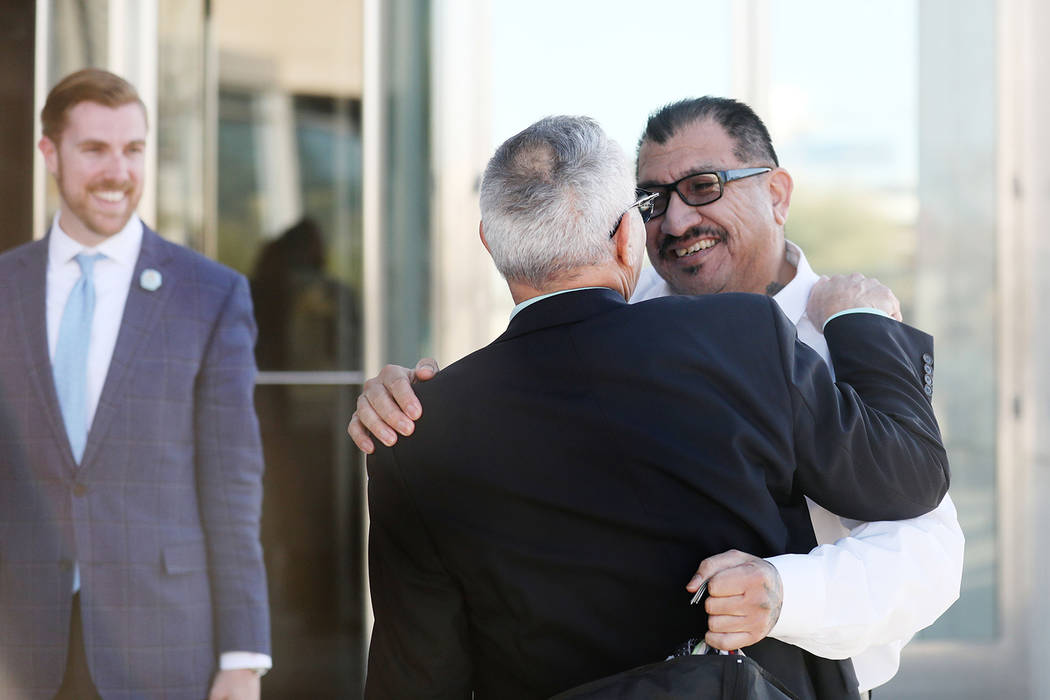 Attorney Shawn Perez hugs defendant Pastor Palafox outside the Lloyd George U.S. Courthouse in ...
