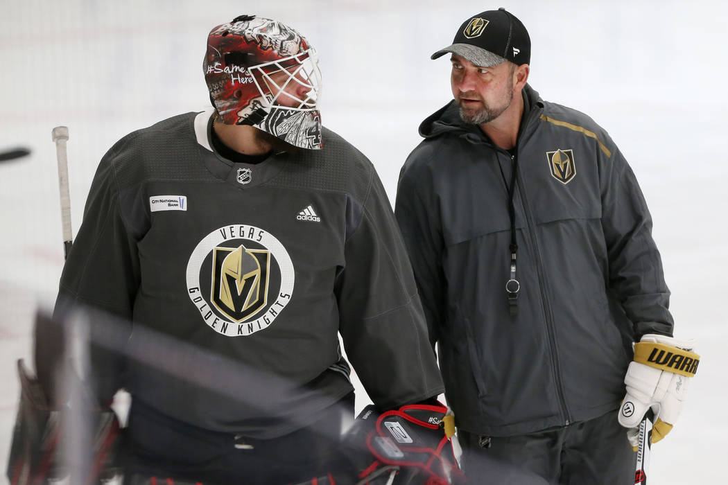 Vegas Golden Knights coach Peter DeBoer, right, talks to new team goaltender Robin Lehner durin ...