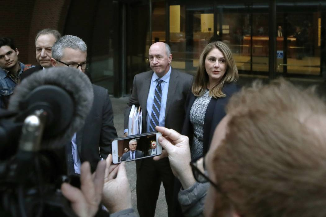 Attorney John Littrell, left and on the screen at center, speaks to the media as client Michell ...