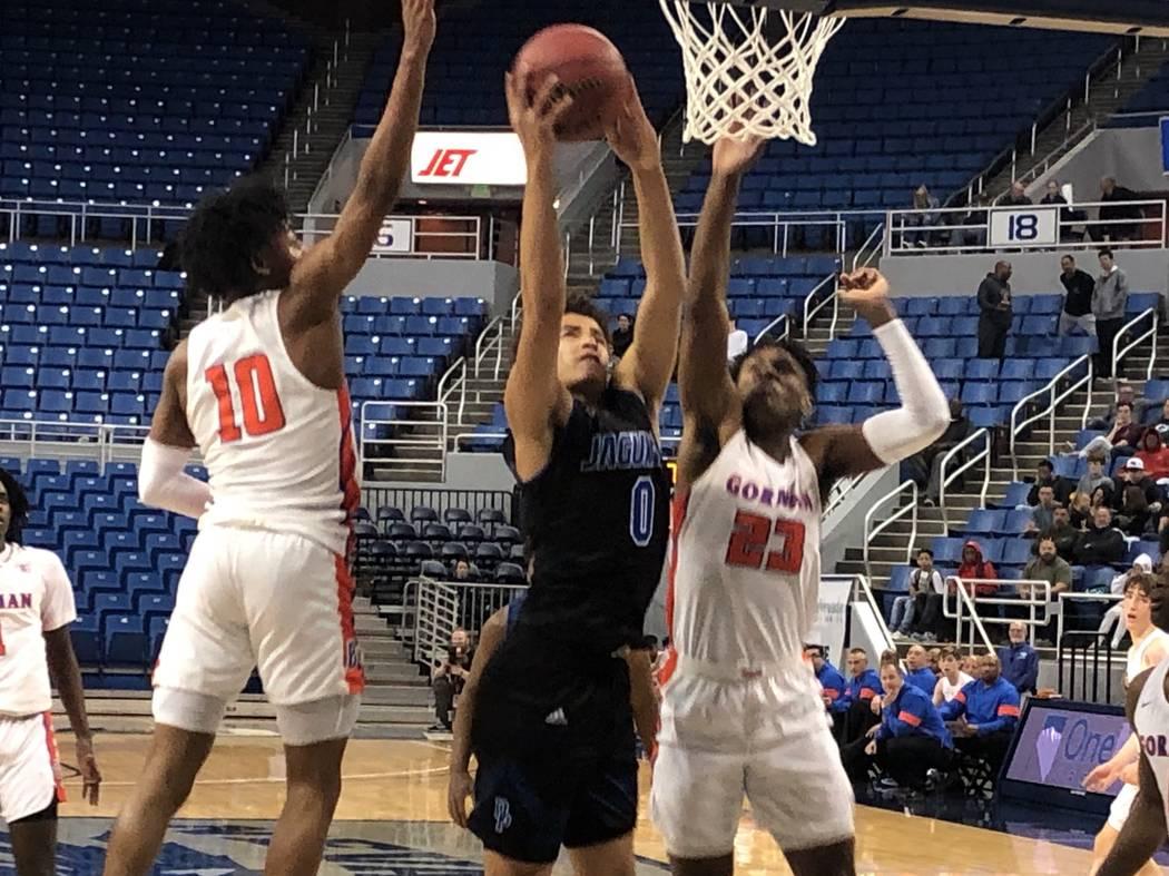 Desert Pines' Anthony Swift (0) goes for a basket between Bishop Gorman defenders Zaon Collins ...