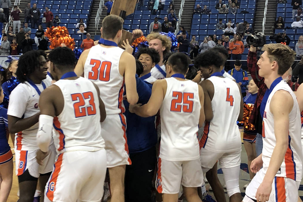 Bishop Gorman players celebrate with the championship trophy after defeating Desert Pines 65-37 ...