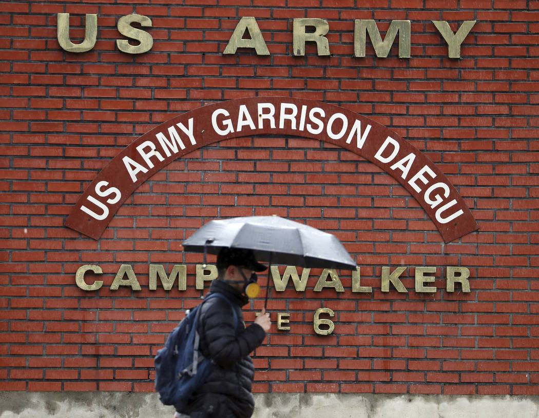 In this Tuesday, Feb. 25, 2020, photo, a man passes by U.S. Army base Camp Walker, in Daegu, So ...