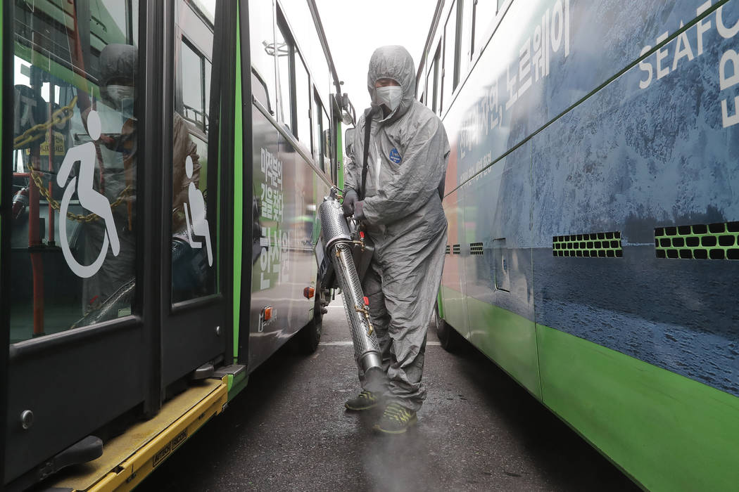 A worker wearing a protective suit sprays disinfectant as a precaution against the coronavirus ...
