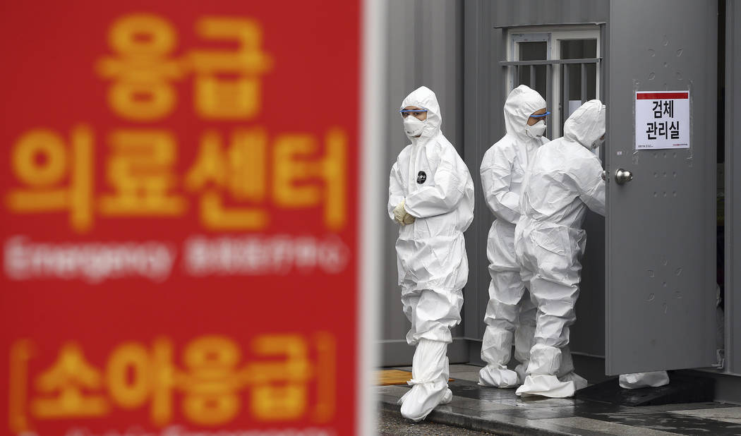 Officials wearing protective attire work to diagnose people with suspected symptoms of the new ...