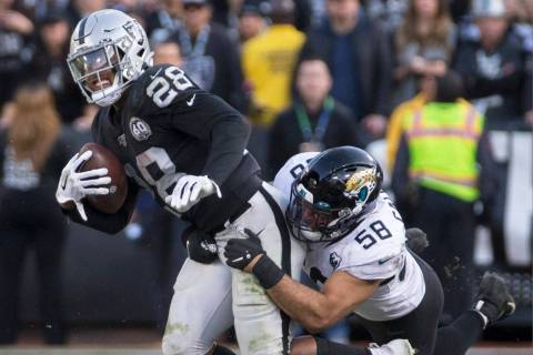 Oakland Raiders running back Josh Jacobs (28) drags Jacksonville Jaguars outside linebacker Aus ...