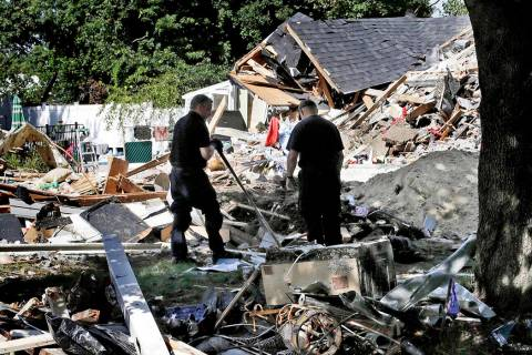 FILE - In this Sep. 21, 2018, file photo, fire investigators pause while searching the debris a ...