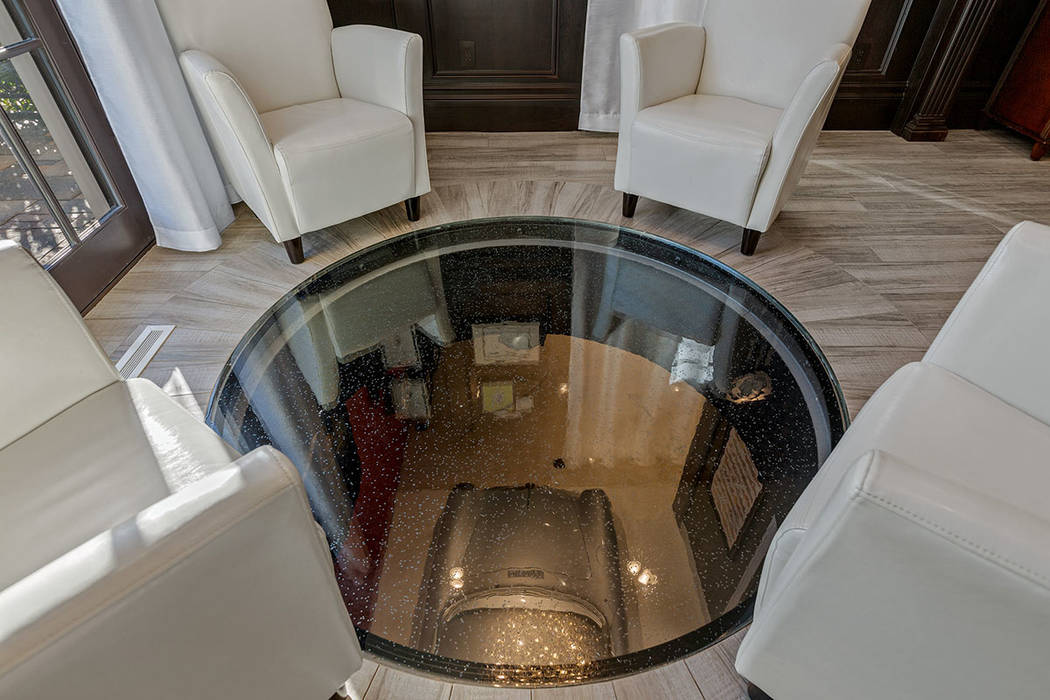 "A ""port hole"" in the office floor offers a view of the classic cars in the garage. (Ivan Sher G ..."