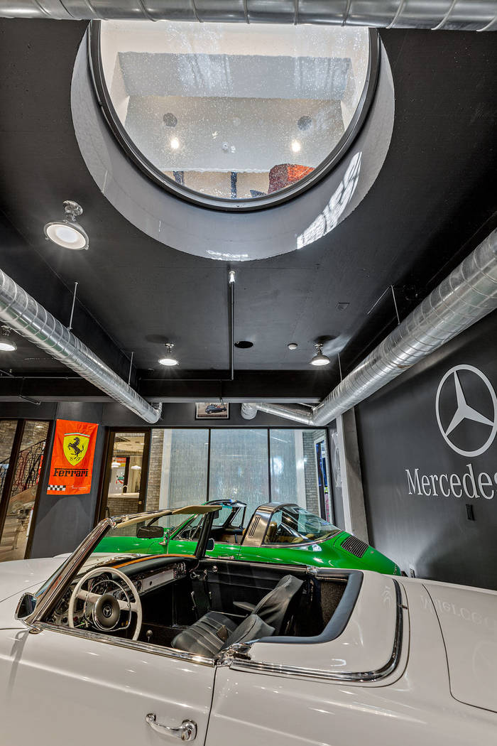 "The cars are displayed in the home through ""port holes"" in the floor. (Ivan Sher Group)"