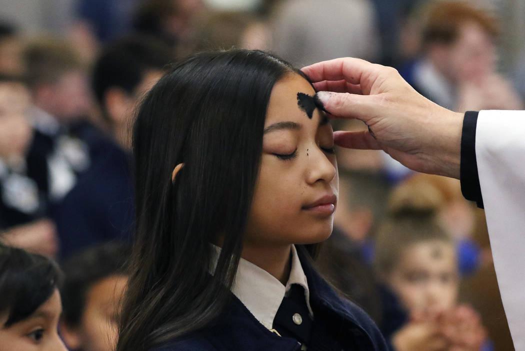 St. Viator Catholic School student Jaila Ann Dela Llana, 12, receives ashes from the Rev. Dan N ...