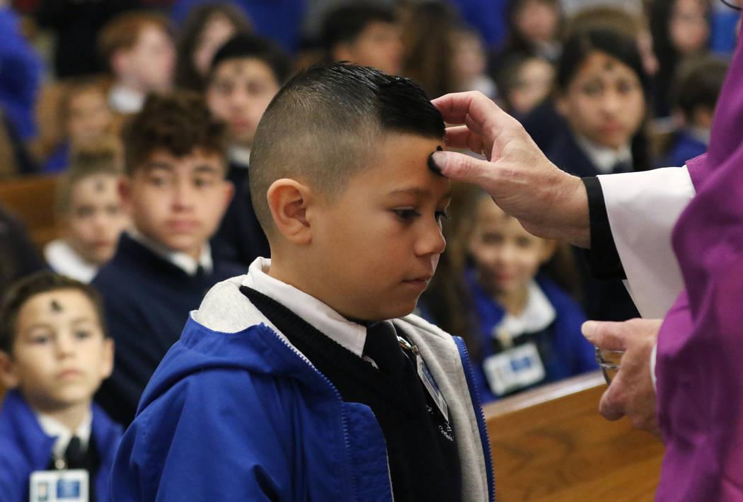St. Viator Catholic Elementary School student Kaden Benito, 6, receives ashes from the Rev. Dan ...
