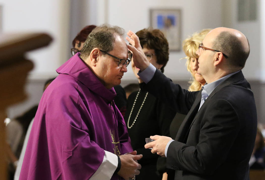 The Rev. Dan Nolan, left, receives ashes from John Keating during Ash Wednesday service at St. ...