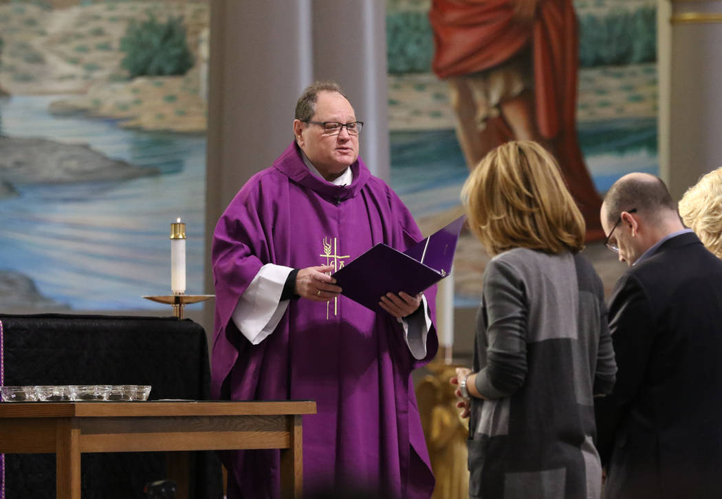 The Rev. Dan Nolan blesses ashes, left, during Ash Wednesday service at St. Viator Catholic Chu ...