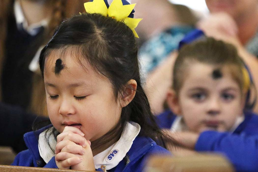 St. Viator Catholic Elementary School student Lilvin Nguyen, 7, prays after receiving ashes dur ...