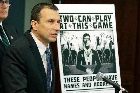 Raymond Duda, FBI Special Agent in Charge in Seattle, speaks as he stands next to a poster that ...