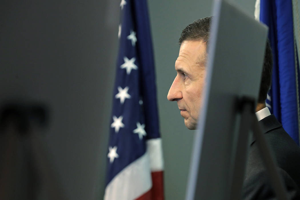 Raymond Duda, FBI Special Agent in Charge in Seattle, stands next to a flag and display boards ...