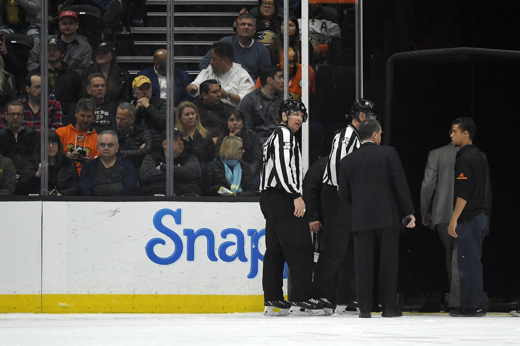 Officials leave the ice after the game between the Anaheim Ducks and the St. Louis Blues was po ...