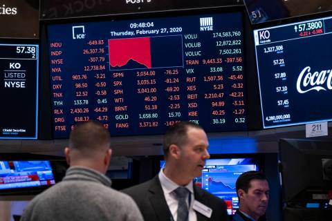 Stocks reflect declines on monitors as people work on the floor of the New York Stock Exchange ...