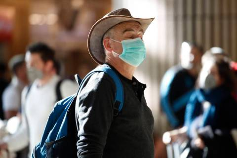 A man wearing a protective mask waits at the arrival hall in Ben Gurion Airport near Tel Aviv, ...