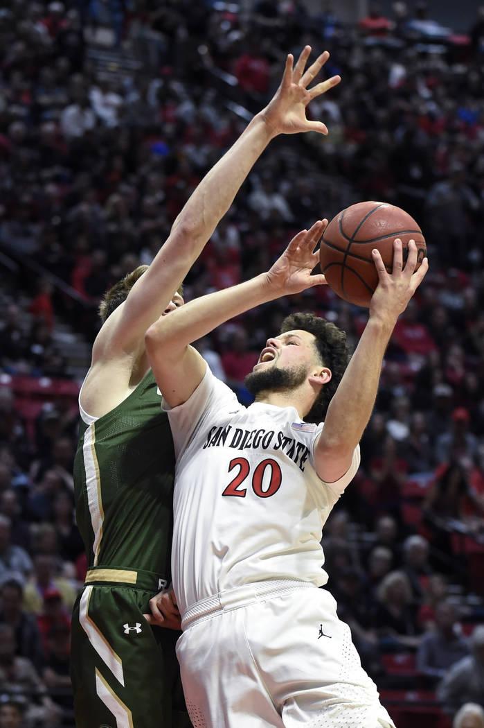 San Diego State guard Jordan Schakel (20) shoots as Colorado State forward Adam Thistlewood def ...