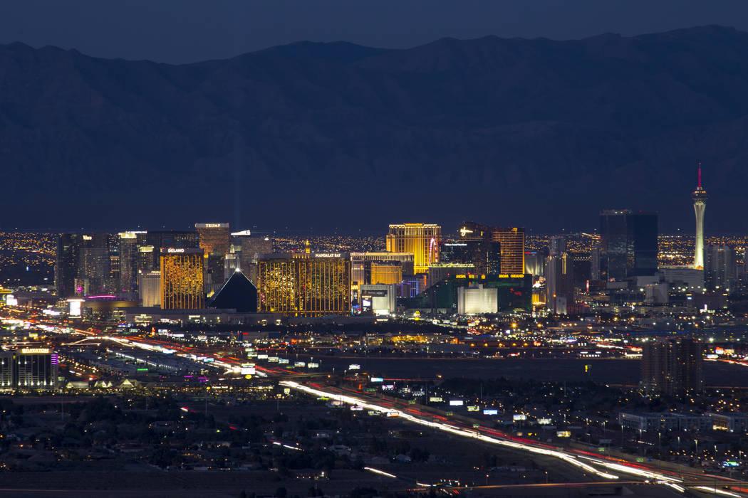 Traffic moves along Interstate 15 as Las Vegas casinos illuminate the city's skyline at dusk on ...