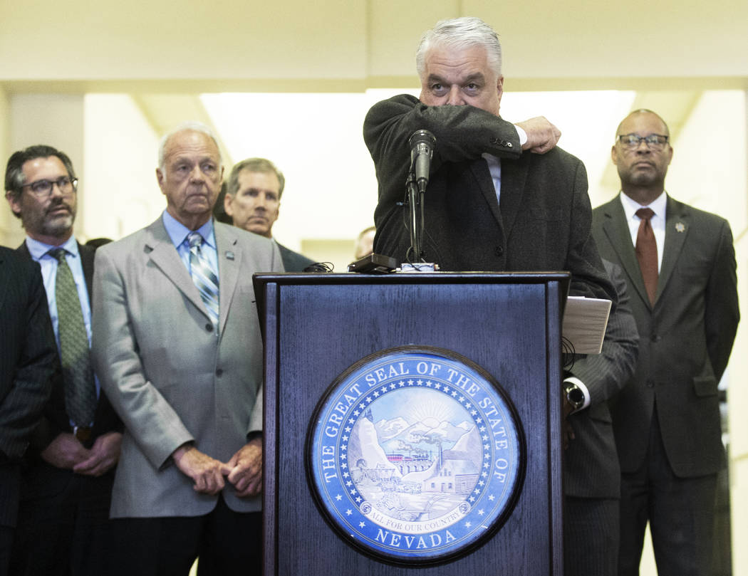 Gov. Steve Sisolak demonstrates the best way to cough without spreading disease during a press ...