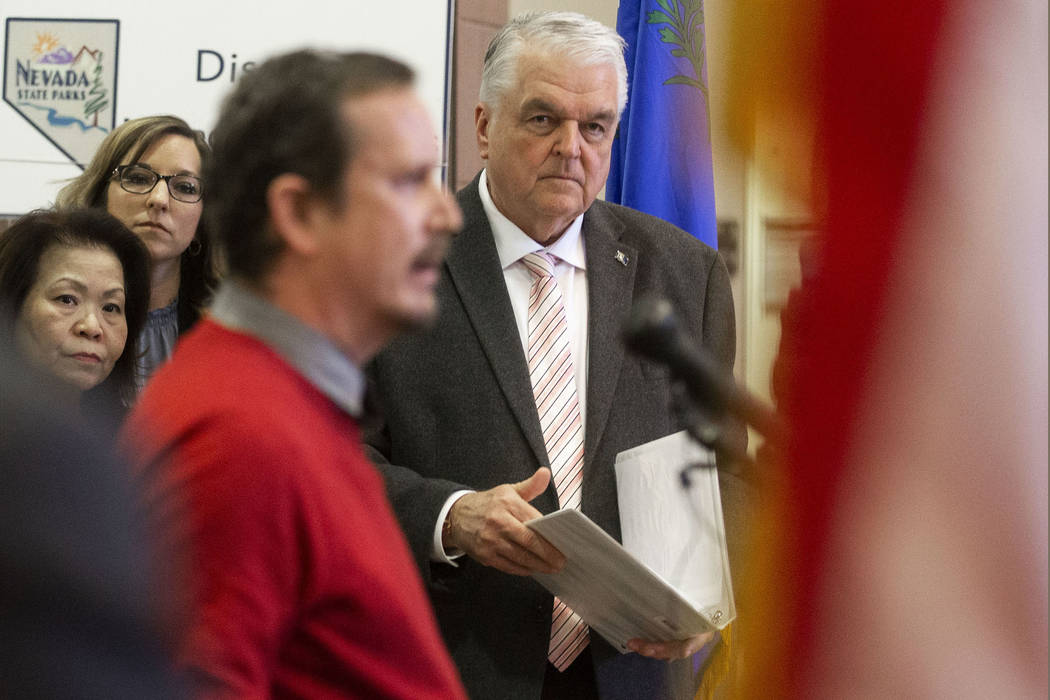 Governor Steve Sisolak, right, waits to speak during a press conference to update the public on ...