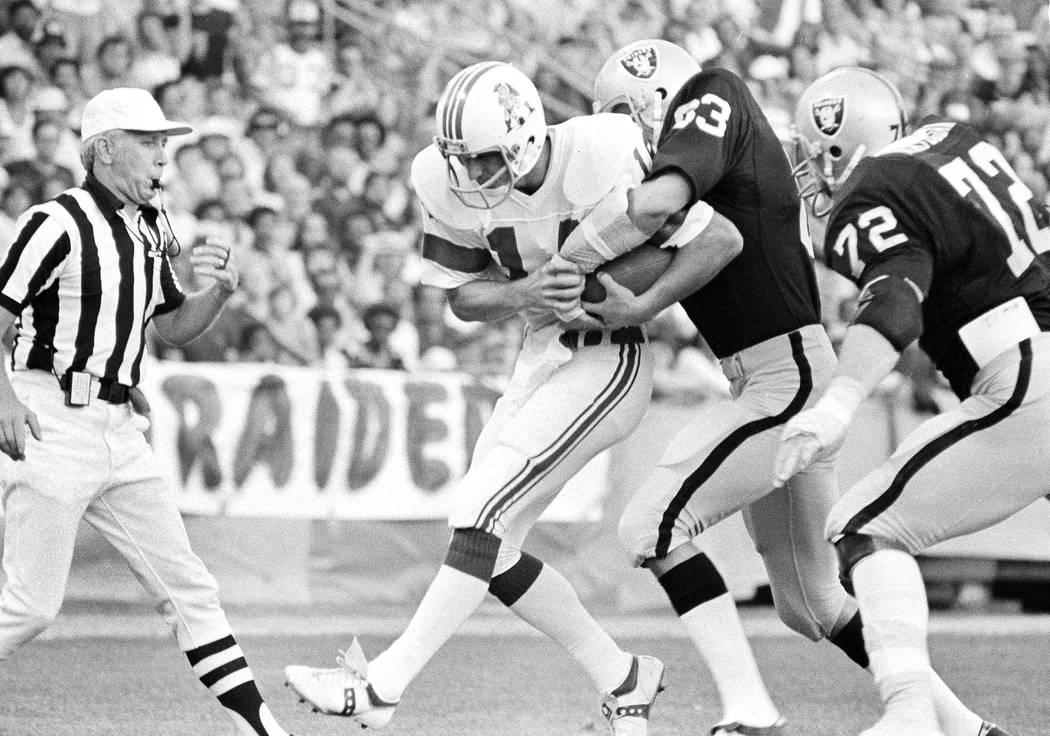 Raiders Ted Hendricks (83) wraps his arms around New England Patriots quarterback Steve Grogan ...