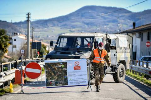 An Italian army soldier blocks off a road leading to the village of Vo'Euganeo, in Italy's nort ...