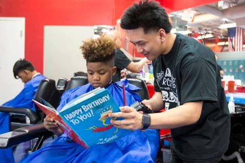 "Barber student Tristian de Guzman reads to Nicholas Lewis, 12, during the third annual ""Re ..."