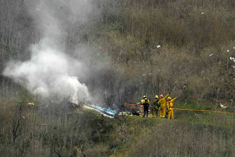 In this Jan. 26, 2020 file photo firefighters work the scene of a helicopter crash where former ...