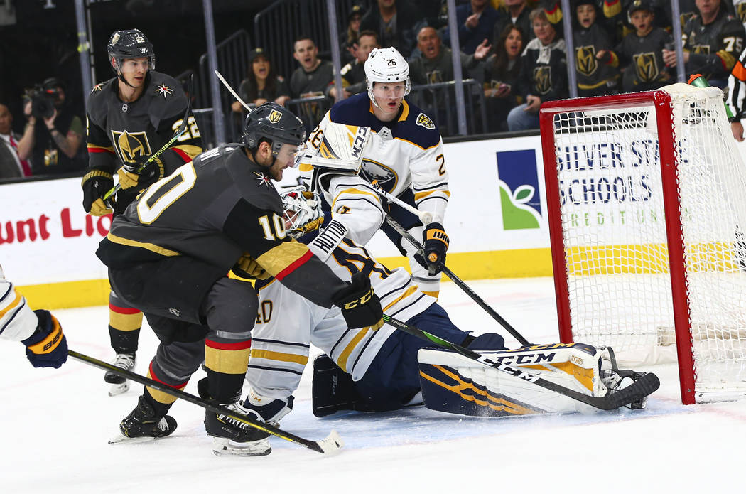 Golden Knights' Nic Roy (10) sends the puck past Buffalo Sabres goaltender Carter Hutton (40) t ...