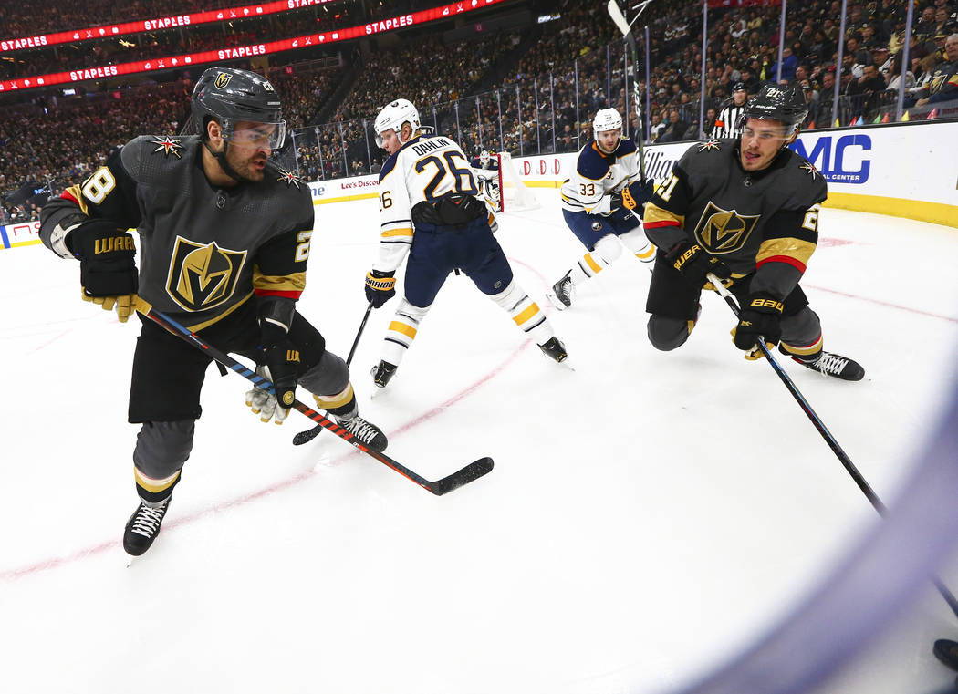 Golden Knights' William Carrier (28) and Nick Cousins (21) manoeuvre the puck around Buffalo Sa ...