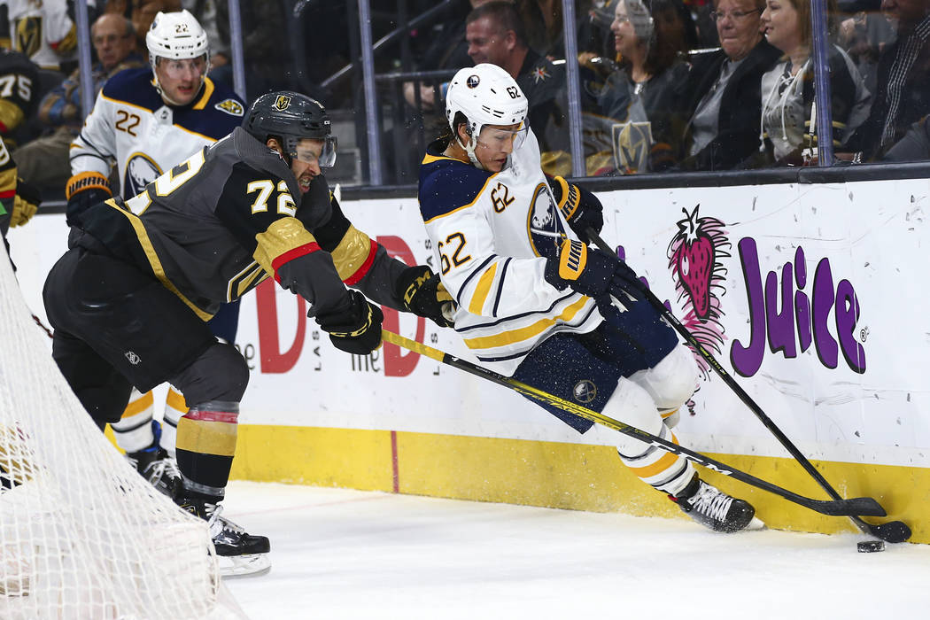 Golden Knights' Gage Quinney (72) battles for the puck against Buffalo Sabres' Brandon Montour ...