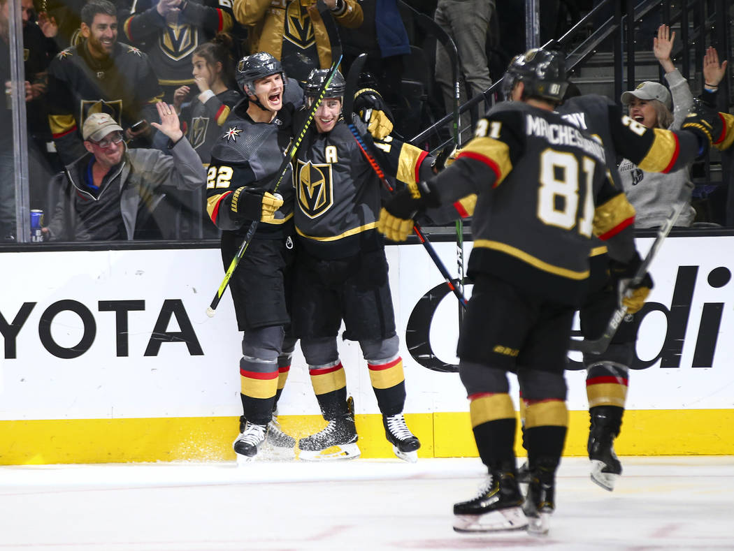 Golden Knights' Nick Holden (22) celebrates a goal by Reilly Smith during the third period of a ...