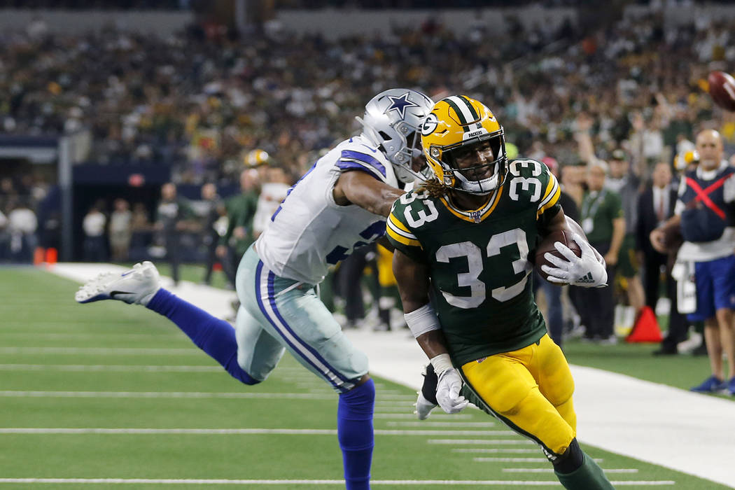 Green Bay Packers' Aaron Jones (33) reaches the end zone for a touchdown in front of Dallas Cow ...