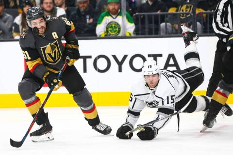Golden Knights' Mark Stone (61) eyes the puck as Los Angeles Kings' Ben Hutton (15) gets trippe ...