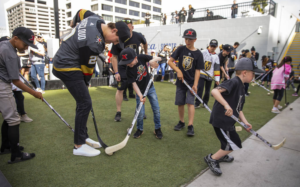 Vegas Golden Knights rookie defenseman Zach Whitecloud, left, plays a little ball hockey with y ...