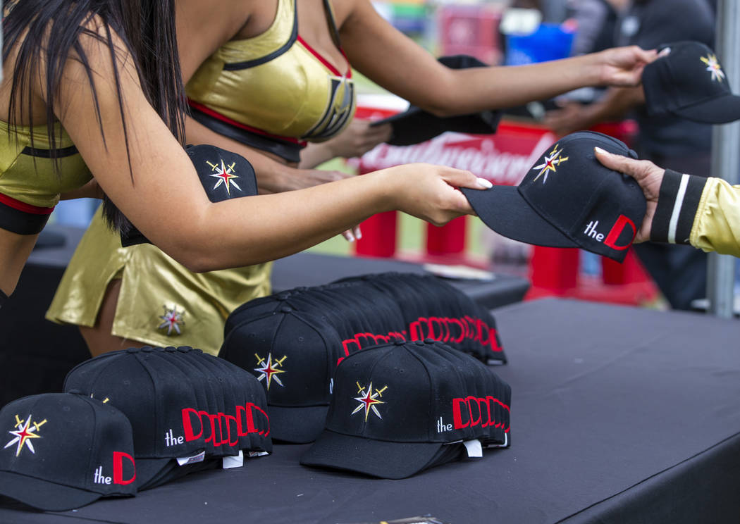 Golden Aces pass out free hats to attendees during the Vegas Golden Knights Fan Fest at the Dow ...