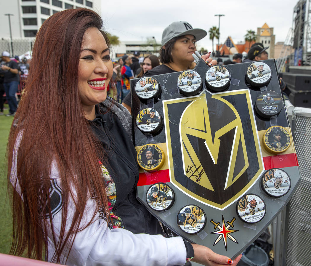 Fan Farrah Stucker shows off a display of player hockey pucks she had made during the Vegas Gol ...