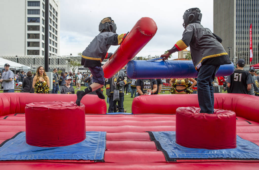 Eric Root, 10, left, is knocked from his perch with a joust from Zi-Ere Davis, 9, as they play ...