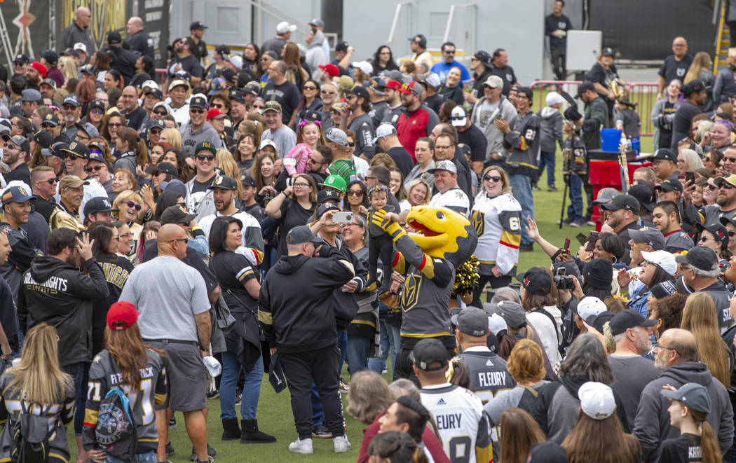 Chance the Gila Monster holds a baby dressed in team gear up to the crowd during the Vegas Gold ...