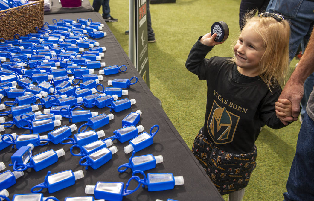Violet Simpson, 3, shows off her hockey puck beside a table of hand sanitizer during the Vegas ...