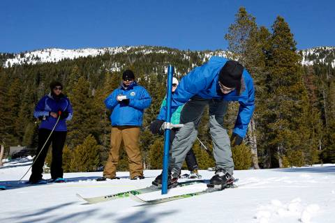 John King, right, of the Department of Water Resources, checks the snowpack depth during the se ...